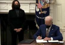 Biden Harris signing signs White House